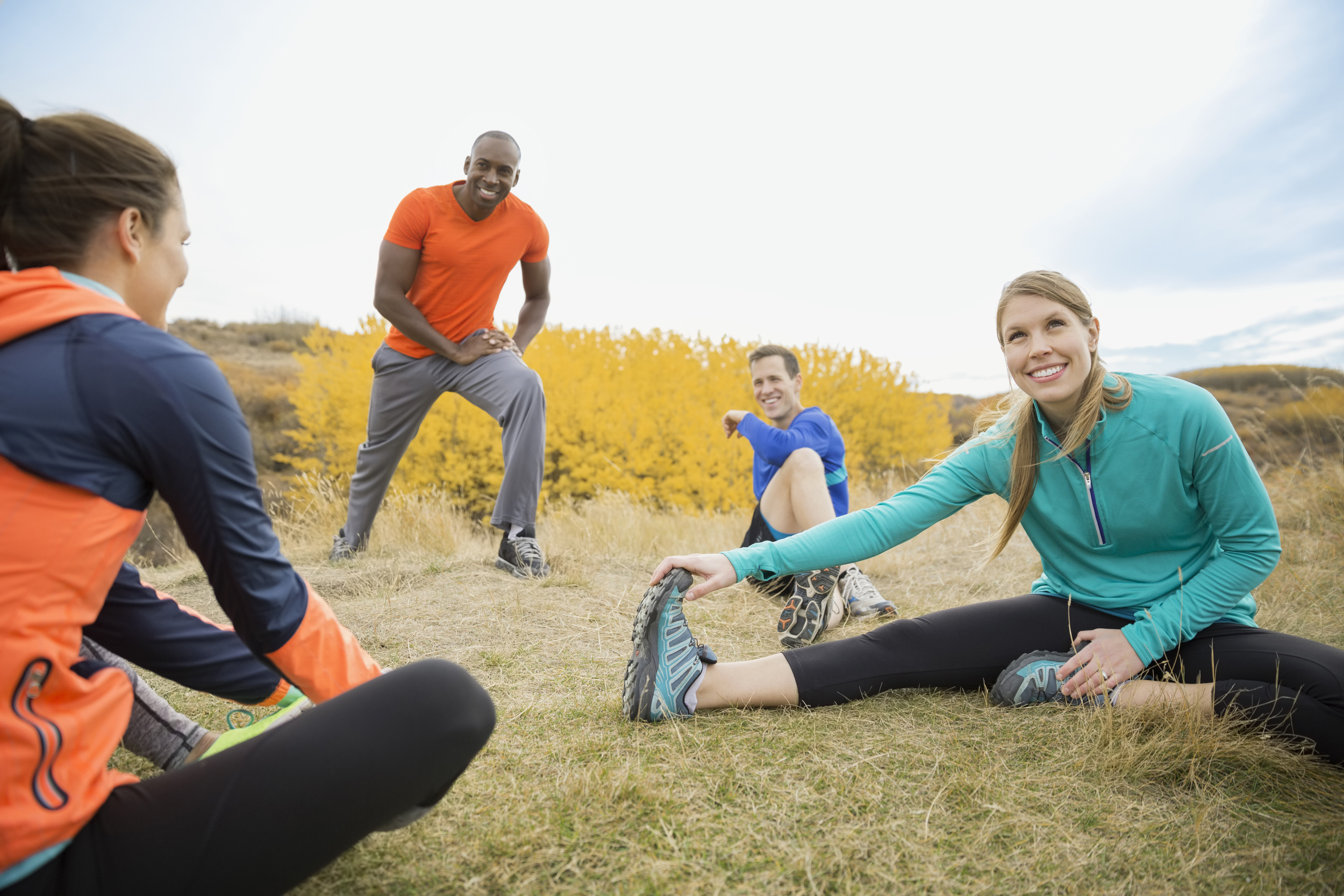 Runners stretching in field