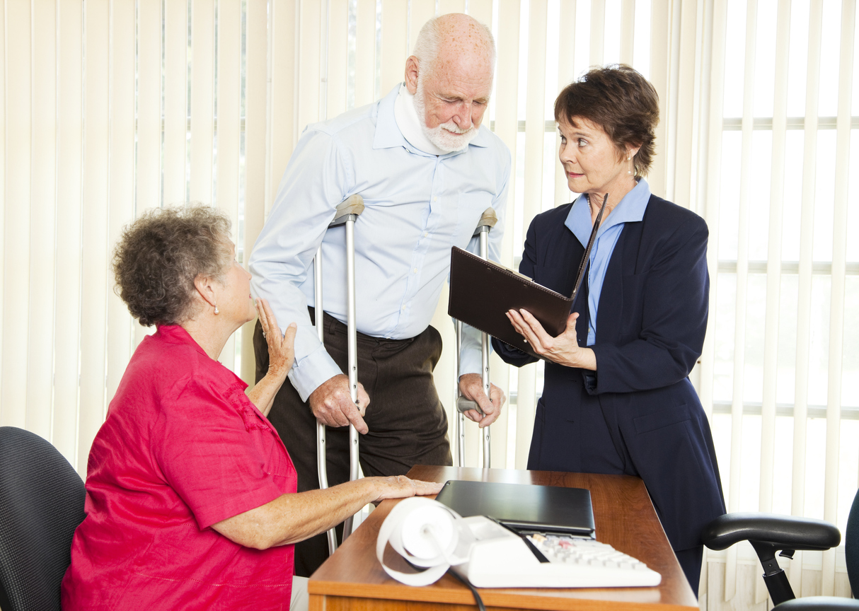 Injured man with crutches with wife meeting lawyer